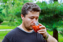 Middle aged man drinks tomato juice on the street Royalty Free Stock Images