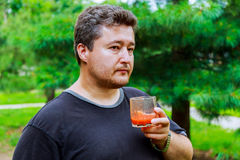 Middle aged man drinks tomato juice on the street. Man Reaching For Middle aged man drinks tomato juice on the street Royalty Free Stock Images