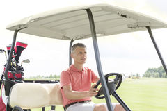 Middle-aged man driving cart at golf course. Middle-aged men driving cart at golf course Royalty Free Stock Photos