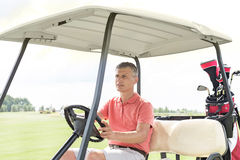 Middle-aged man driving cart at golf course. Middle-aged men driving cart at golf course Royalty Free Stock Images