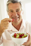 Middle Aged Man Eating Fresh Fruit Royalty Free Stock Photo