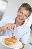 Middle Aged Man Eating Fresh Grapefruit Stock Photography