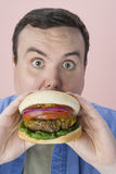 Middle Aged Man Eating Hamburger Royalty Free Stock Image