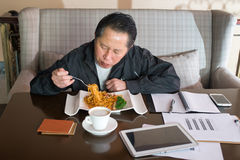 Middle-aged man eating noodles Stock Photos