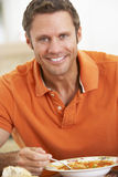 Middle Aged Man Eating Soup, Smiling At The Camera Royalty Free Stock Image