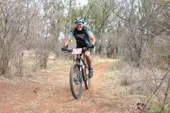Middle aged man enjoying outdoors ride at Mountain Bike Race Stock Image