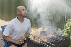 Middle-aged man enjoys cooking meat on the grill. leisure, food, people and holidays concept - happy young man cooking meat on bar. Becue grill at outdoor summer Royalty Free Stock Image