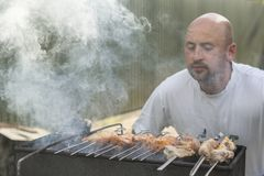 Middle-aged man enjoys cooking meat on the grill. leisure, food, people and holidays concept - happy young man cooking meat on bar. Becue grill at outdoor summer Royalty Free Stock Images