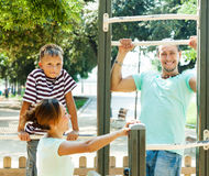 Middle-aged man with family training on chin-up bar Royalty Free Stock Image