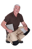Middle-aged man fitting tiles Stock Photography