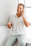 Middle aged man with gadget. Handsome middle aged man in casual clothes is talking on the mobile phone and smiling while sitting near the window at home Stock Image