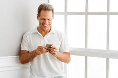 Middle aged man with gadget. Handsome middle aged man in casual clothes is using a smart phone and smiling while sitting near the window at home Royalty Free Stock Photos