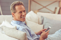 Middle aged man with gadget. Handsome middle aged man is using a smartphone, looking at camera and smiling while sitting on sofa at home Stock Photography
