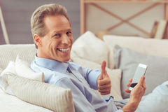 Middle aged man with gadget. Handsome middle aged man is using a smartphone, showing Ok sign and smiling while sitting on sofa at home Royalty Free Stock Photos