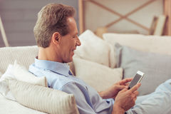 Middle aged man with gadget. Handsome middle aged man is using a smartphone and smiling while sitting on sofa at home Stock Photography