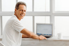 Middle aged man with gadget. Side view of middle aged man using a laptop and smiling while sitting on a chair near the window at home stock images