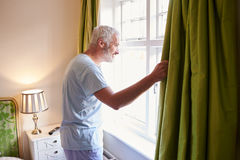 Middle aged man gets up and opens the curtains in hotel room Stock Photos