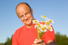 Middle-aged man giving flowers. Middle-aged man smiling and giving flowers Royalty Free Stock Photos