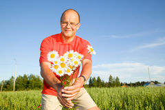 Middle-aged man giving flowers. Middle-aged man smiling and giving flowers Royalty Free Stock Photography