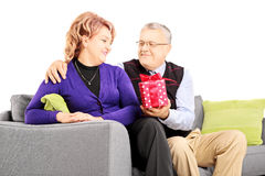 Middle aged man giving a present to his wife Stock Photo
