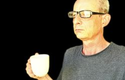Middle aged man with glasses holding a white cup. Portrait of mature man on black background. Copy space stock photo