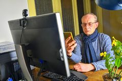Middle aged man with glasses sitting at desk. Mature man using mobile phone. Senior concept. Man at home office stock image
