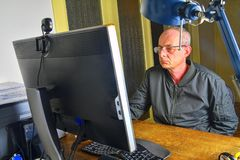 Middle aged man with glasses sitting at desk. Mature man using personal computer. Senior concept royalty free stock photo