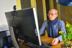 Middle aged man with glasses sitting at desk. Mature man using personal computer. Senior concept. Man working at home stock images