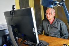 Middle aged man with glasses sitting at desk. Mature man using personal computer. Senior concept. Man working at office stock images