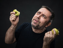 Middle-aged man with a green apples Stock Images