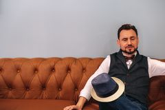 A middle-aged man in a hat sits on a leather sofa. royalty free stock images