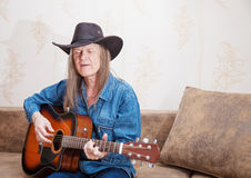 Middle-aged man in a hat plays guitar and sings Royalty Free Stock Photography