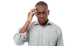 Middle aged man having headache. Sad faced African guy suffering from headache Stock Photography
