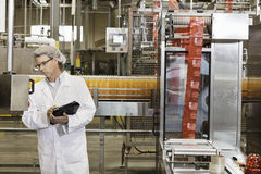 Middle-aged man having inspection at bottling industry. Middle-aged men having inspection at bottling industry Royalty Free Stock Image