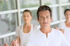 Middle aged man in the head of group of people doing yoga Stock Photo