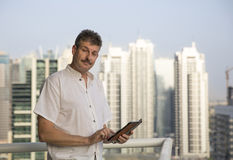 Middle aged man at his balcony overlooking the marina, holding a Stock Photography
