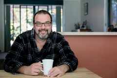 Man Smiling drinking his morning coffee royalty free stock photography