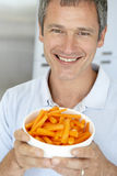 Middle Aged Man Holding A Bowl Of Carrots Royalty Free Stock Photo