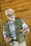 Middle-aged man holding fishing rod Stock Photos