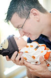Middle aged man holding newborn stock photos