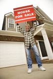 Middle-aged man holding a for sale sign. Portrait of middle-aged African-American male outside house holding up for sale sign Royalty Free Stock Image