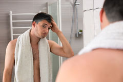 Middle-aged man holding towel on his shoulders while correcting Stock Photos