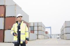 Middle-aged man holding walkie-talkie in shipping yard Royalty Free Stock Photo