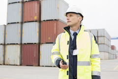 Middle-aged man holding walkie-talkie in shipping yard Royalty Free Stock Images