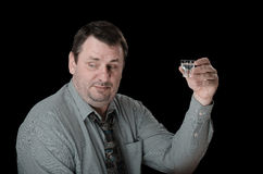 Middle aged man holds shot of vodka. And looking down Royalty Free Stock Photography