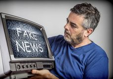 Middle-aged man holds a TV with fake news screen stock photography