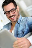 Cheerful man using tablet Stock Images