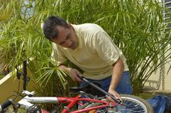 Middle-aged man inflating bicycle Stock Photography