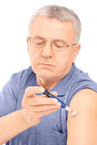 Middle aged man injecting insulin in his arm Royalty Free Stock Photography