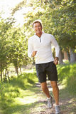 Middle Aged Man Jogging In Park Royalty Free Stock Images